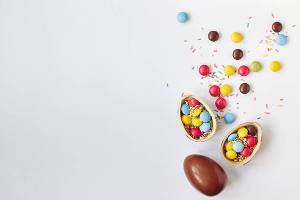 Chocolate Easter eggs and sweets on white background stock photo