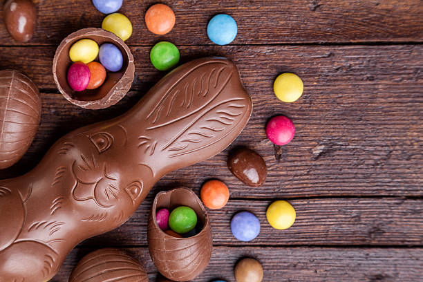 chocolate easter eggs and sweets on wooden background - easter bunny stock photos and pictures