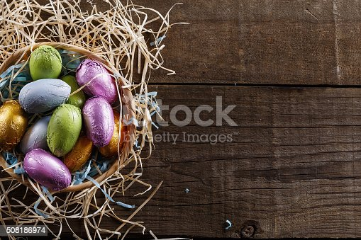 Chocolate Easter eggs in a straw basket over rustic wooden background with copyspace. Top view, Rustic style