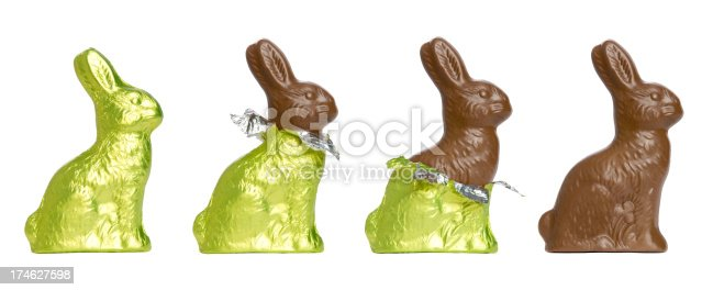 A chocolate Easter rabbit in various stages of unwrap. Set against a pure white background.