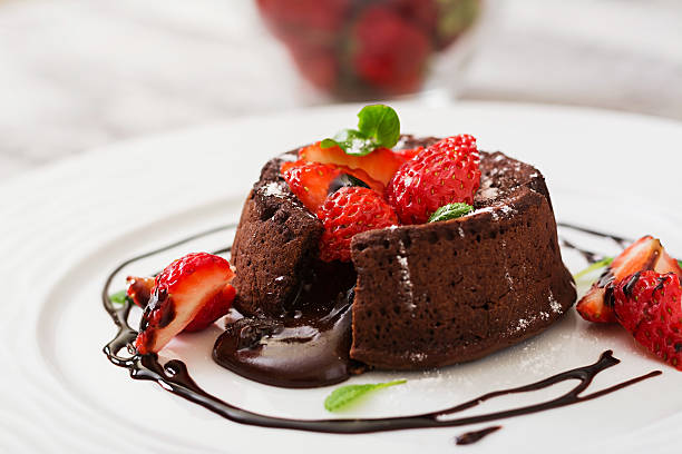 chocolate fondant (cupcake) with strawberries and powdered sugar - tatlı stok fotoğraflar ve resimler