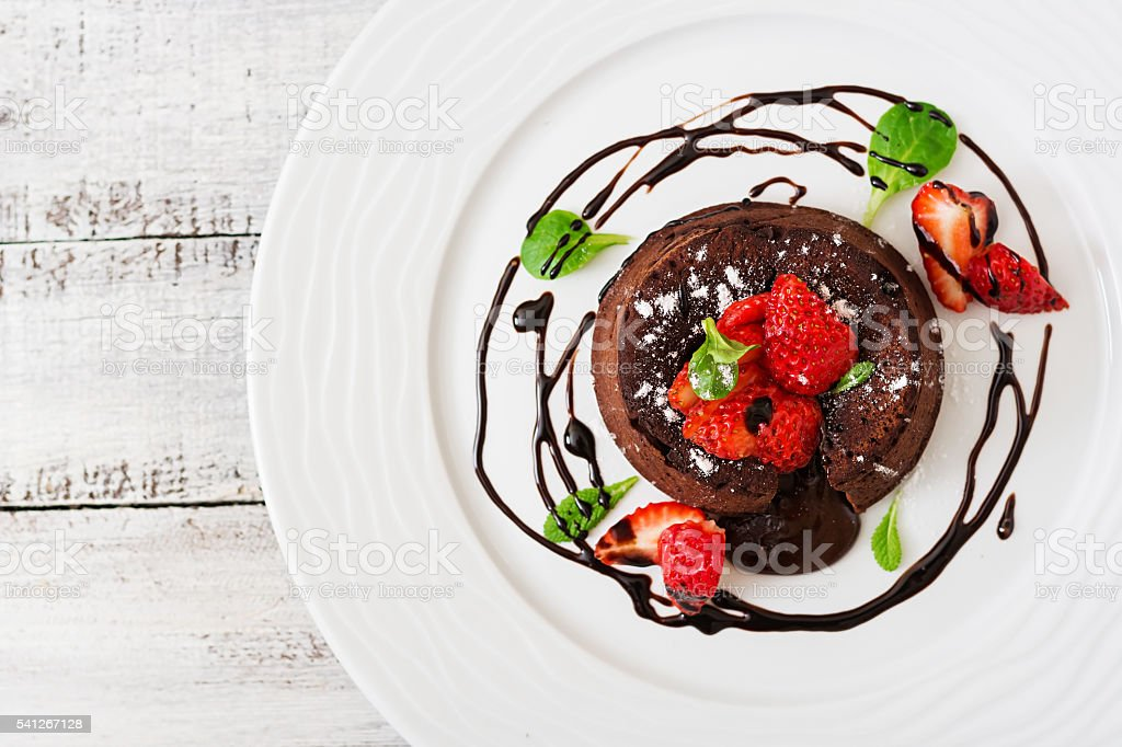 Chocolate fondant (cupcake) with strawberries and powdered sugar. Top view stock photo