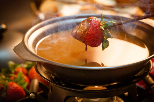 Chocolate fondue Chocolate fondue with oven on wooden table chocolate fondue stock pictures, royalty-free photos & images