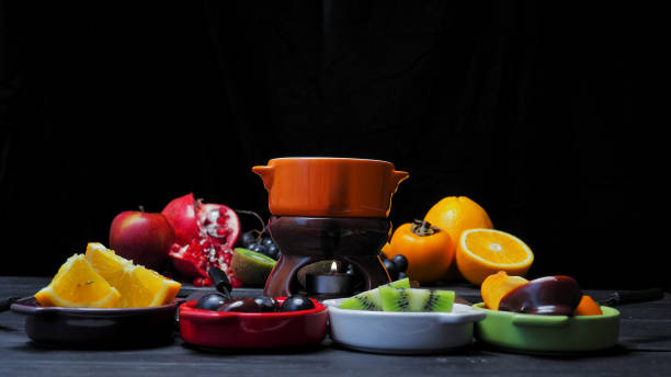 Chocolate fondue Chocolate fondue with various fresh fruit: orange, red grapes, kiwi, persimmon and others. Vibrant colors over black background chocolate fondue stock pictures, royalty-free photos & images
