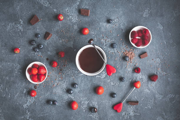 Chocolate fondue with fresh berries on dark background Chocolate fondue with fresh berries on dark background. Valentine's Day. Flat lay, top view chocolate fondue stock pictures, royalty-free photos & images