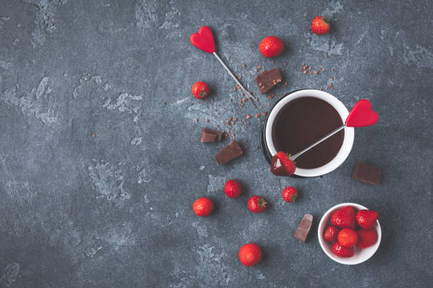 Chocolate fondue with fresh strawberry on dark background Chocolate fondue with fresh strawberry on dark background. Valentine's Day. Flat lay, top view chocolate fondue stock pictures, royalty-free photos & images