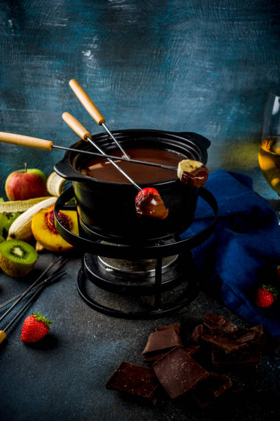 Chocolate fondue with fruit and berry Chocolate fondue in traditional fondue pot, with forks, white wine, assorted various berries and fruit, copy space chocolate fondue stock pictures, royalty-free photos & images