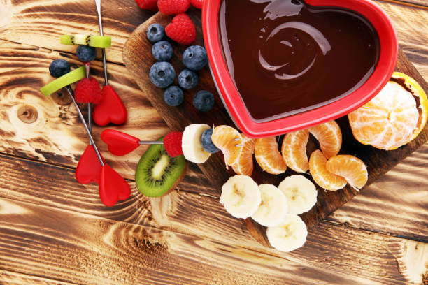 chocolate fondue with fruits assortment on wooden cutting board chocolate fondue with fruits assortment on wooden cutting board chocolate fondue stock pictures, royalty-free photos & images