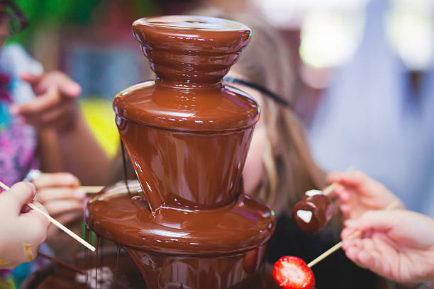 Chocolate Fountain With Fondue, Fruits and Marshmallow on children party Vibrant Picture of Chocolate Fountain Fontain on childen kids birthday party with a kids playing around and marshmallows and fruits dip dipping into fountain chocolate fondue stock pictures, royalty-free photos & images