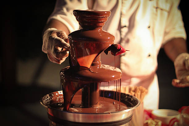 Chocolate Fountain with Strawberry Schokoladenbrunnen Chef is preparing a strawberry skewer under a chocolate fountain/ Schokoladenbrunnen chocolate fondue stock pictures, royalty-free photos & images