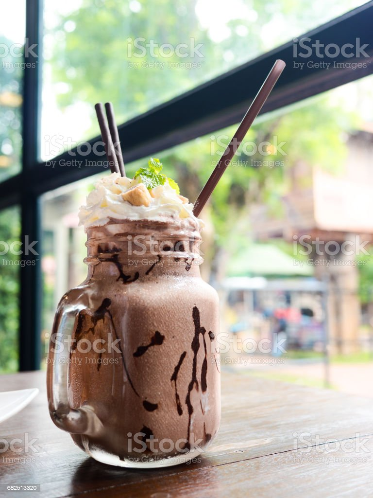 Chocolate frappe with whipped cream, mint and biscuit roll on wooden table. Selective focus. Стоковые фото Стоковая фотография