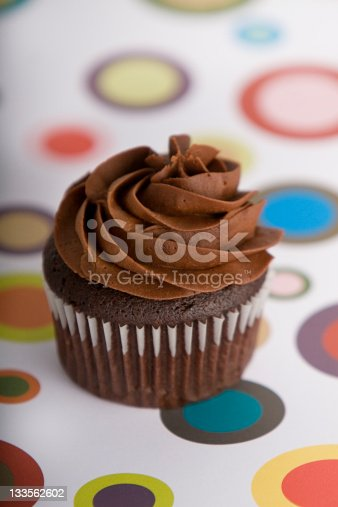 a closeup photo of a wooden spoon stirring a pot of melted chocolate fudge