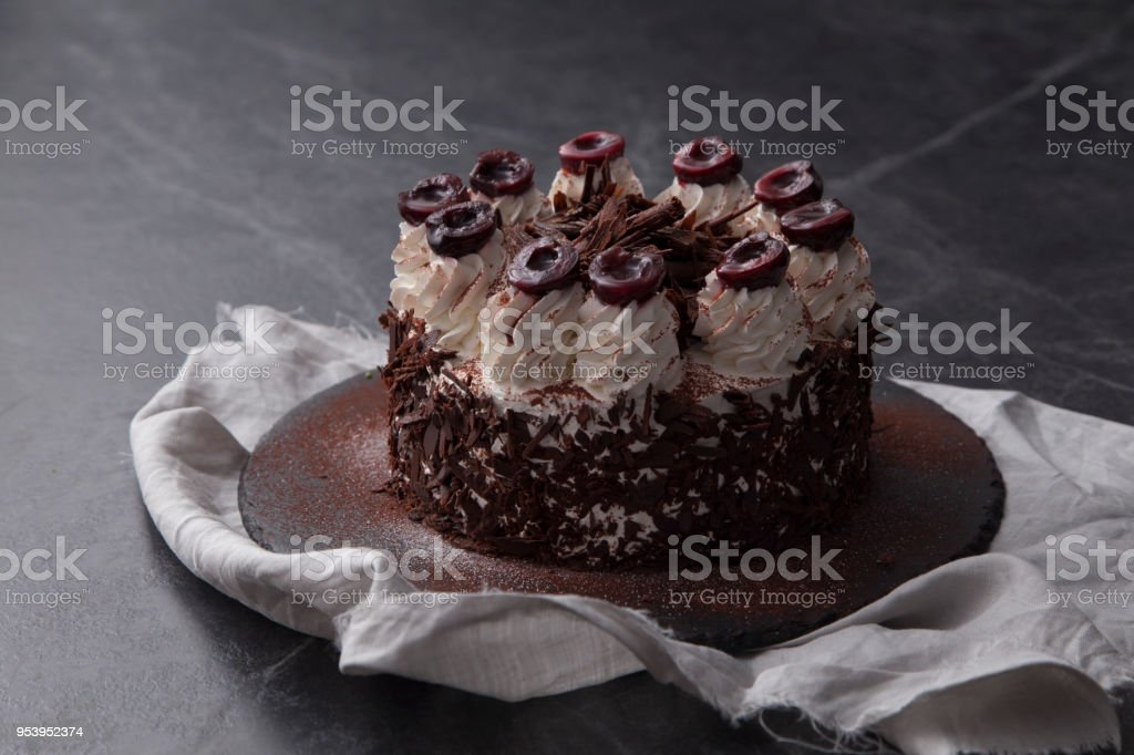 Chocolate Fudge Cake Decorated With Chocolate Curl On Black Table