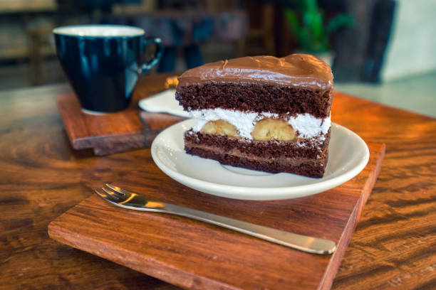 schokoladenfondant mit weißen sahne und banane auf weißen teller und heißen kaffee hintergrund auf holztisch. - gebackene banane stock-fotos und bilder