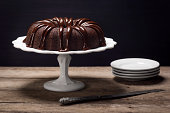 A chocolate bundt cake with ganache icing sits atop a cake stand on a wooden table.