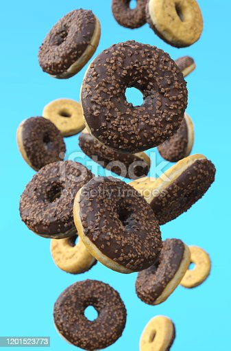 istock Chocolate glazed doughnuts in motion against blue background. 1201523773