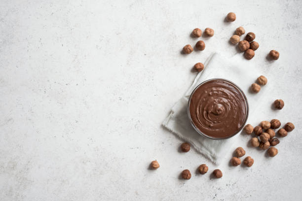 Chocolate Hazelnut Spread Chocolate Hazelnut Spread on white background, top view, copy space. Homemade chocolate spread with hazelnuts. theobroma stock pictures, royalty-free photos & images