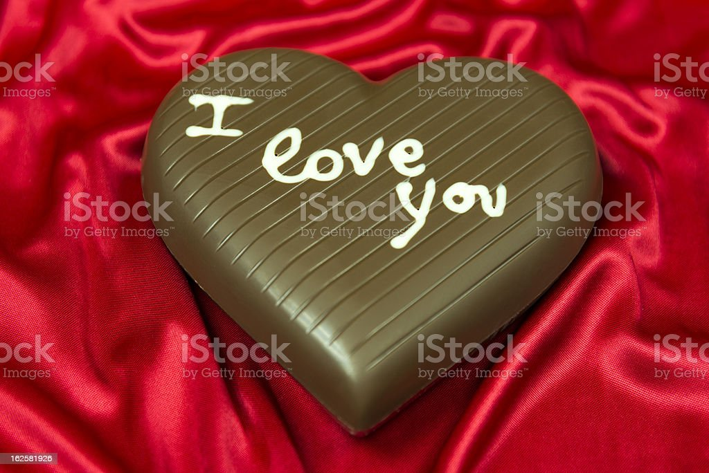 chocolate heart on red satin royalty-free stock photo