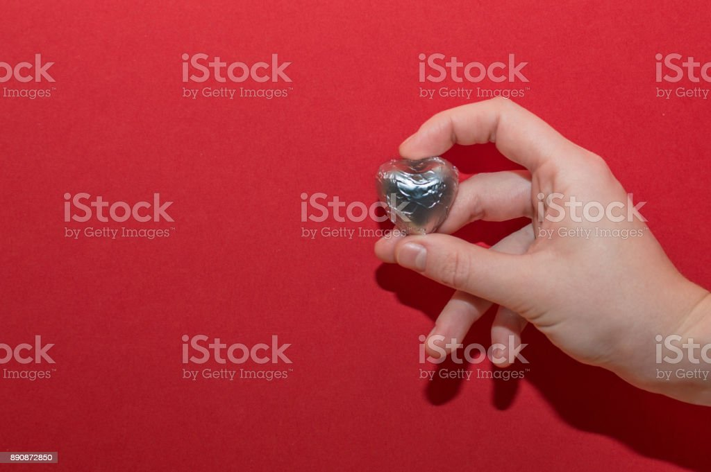 Chocolate heart shaped sweet holding by female hand on red background. Beautiful charity and healtcare concept. stock photo