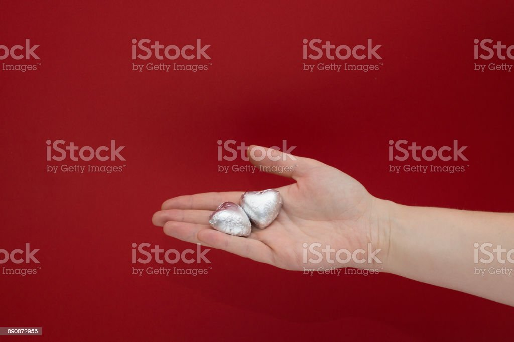Chocolate heart shaped sweets in the foil laying on a female hand on red background. Beautiful charity and healtcare concept. stock photo