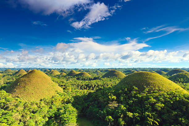 chocolate hills under blue sky in the philippines. - philippines stock photos and pictures
