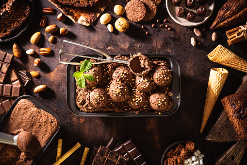 Chocolate ice cream scoop ball, waffle cone, chocolates and mint leaf, toppings and ingredients