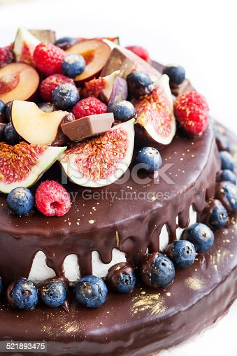 472311978 istock photo Chocolate icing cake, decorated with fresh fruit 521893475