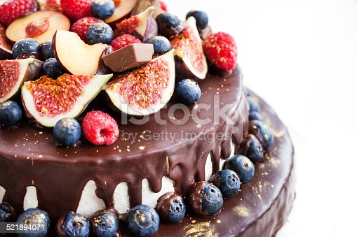472311978 istock photo Chocolate icing cake, decorated with fresh fruit 521894071