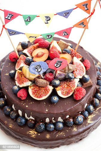 472311978 istock photo Chocolate icing cake, decorated with fresh fruit 521895603