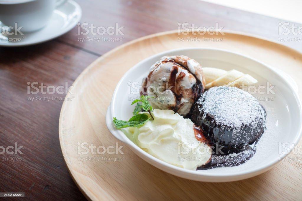 Chocolate lava cake with vanilla ice cream ball, banana and whipped cream stock photo