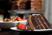 Piece of delicious chocolate cake with berries on wooden table