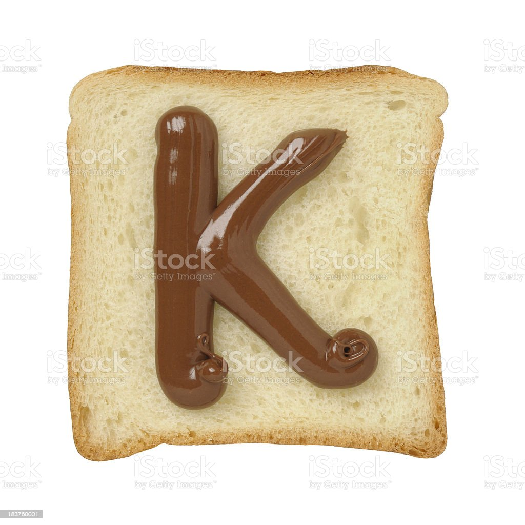 Chocolate letter K on a tinloaf slice, white background royalty-free stock photo