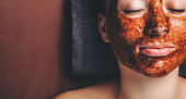 Chocolate mask applied on the woman's face while she is lying with closed eyes near free space