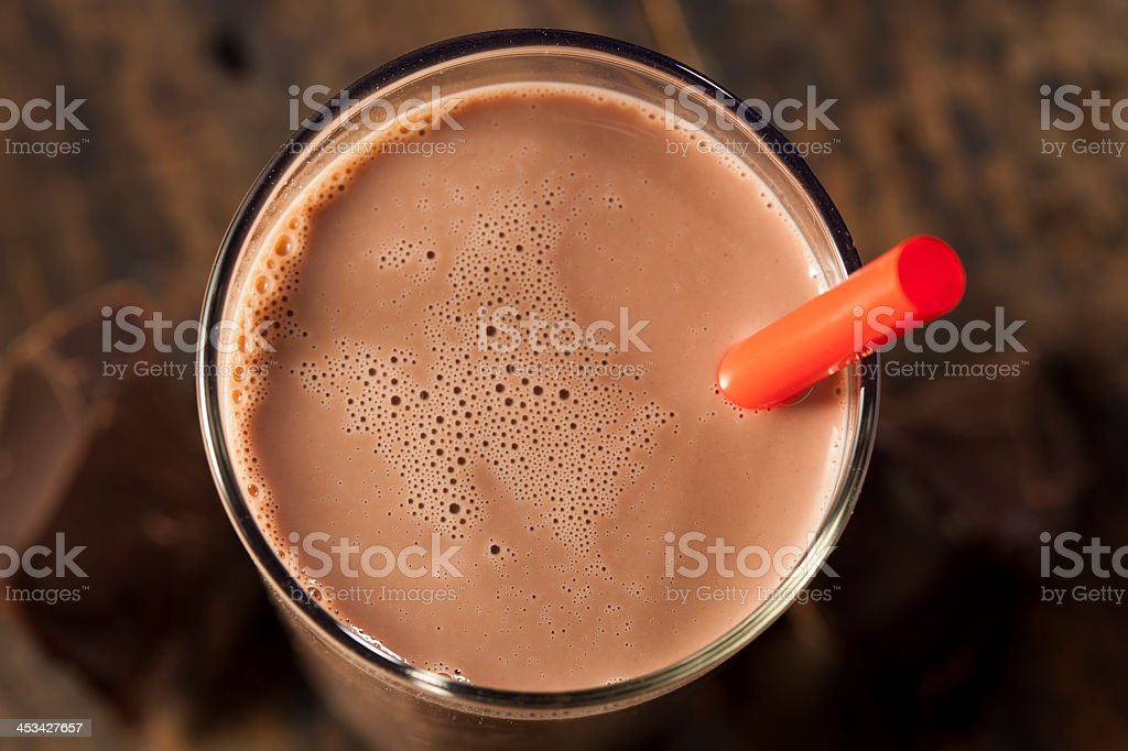 Chocolate milk on a glass with red straw stock photo