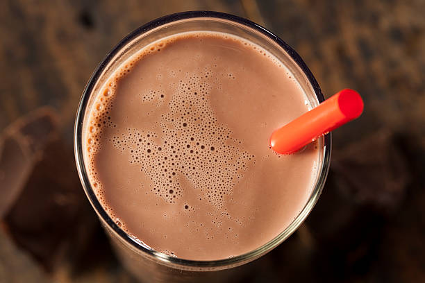 Chocolate milk on a glass with red straw Refreshing Delicious Chocolate Milk with Real Cocoa chocolate milk stock pictures, royalty-free photos & images