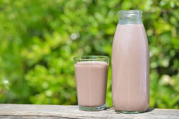 Chocolate milk Chocolate milk in the bottle and in the cup outdoors chocolate milk stock pictures, royalty-free photos & images