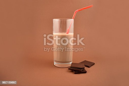 Chocolate milk with chocolate pieces. Glass of chocolate milk on a brown background