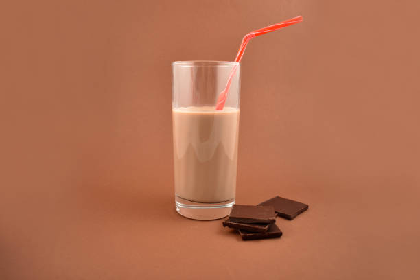Chocolate milk stock images Chocolate milk with chocolate pieces. Glass of chocolate milk on a brown background chocolate milk stock pictures, royalty-free photos & images
