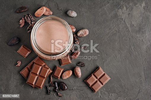 istock Chocolate milk with pieces of chocolate bar and cacao beans 635924682
