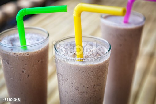 3 glasses with chocolate milkshake with colored straws