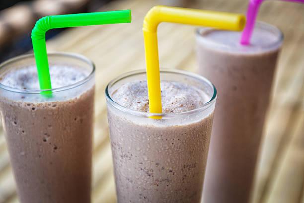 Chocolate milkshakes 3 glasses with chocolate milkshake with colored straws chocolate milk stock pictures, royalty-free photos & images