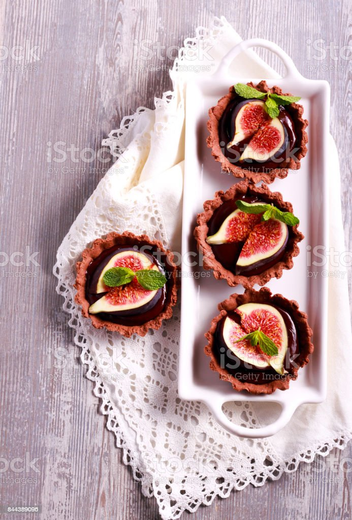 Chocolate mini tarts with chocolate filling and fig on top stock photo