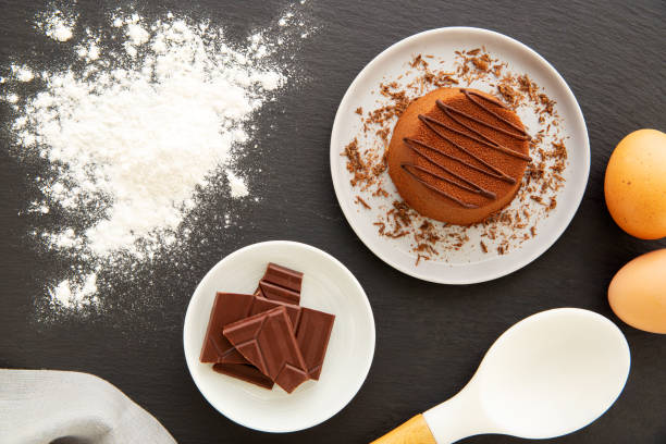 Chocolate Moelleux cake or molten cake in a grey plate filled with grated chocolate, spilled flour, eggs, chocolate pieces and napkin over a slate. Flat lay. stock photo