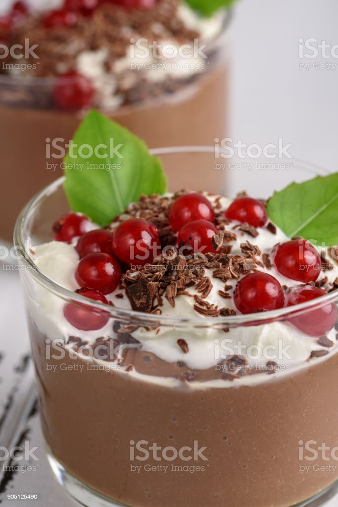 Chocolate mousse with currant and mint in a glasses on a whiite wooden background. stock photo