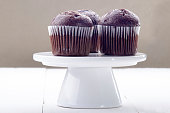 chocolate muffin on a white porcelain cake stand