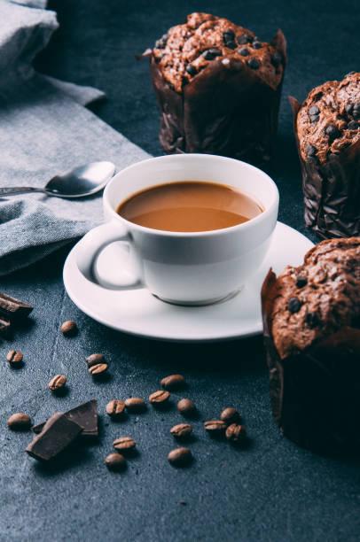 schokoladen-muffins und kaffee auf einem dunklen hintergrund - heiße schokoladen cupcakes stock-fotos und bilder