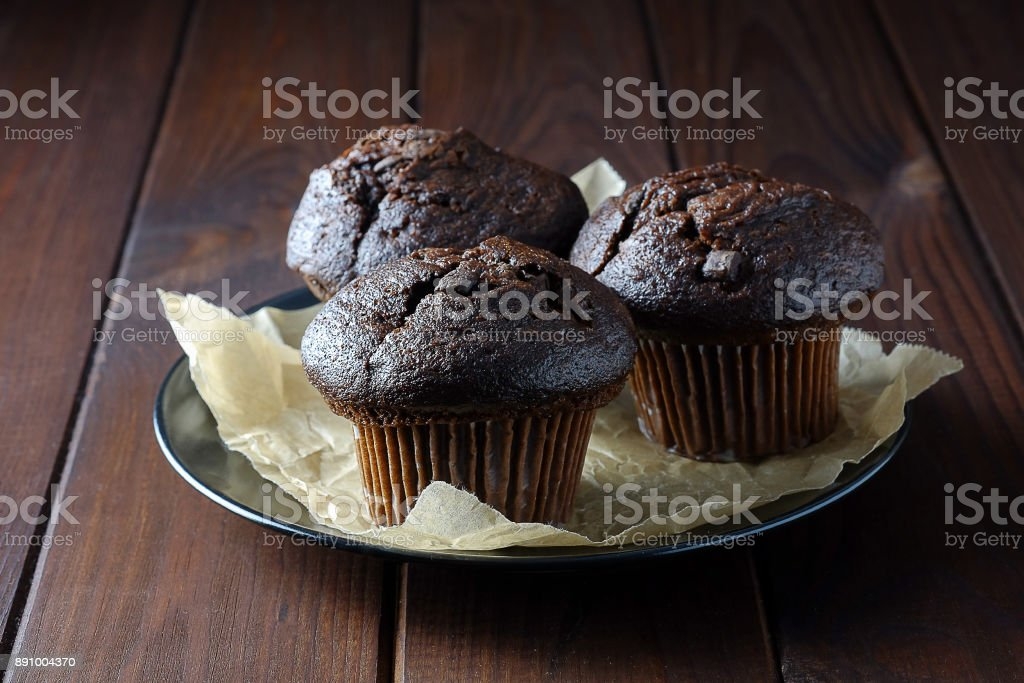 Chocolate muffins on a plate on a dark background. stock photo