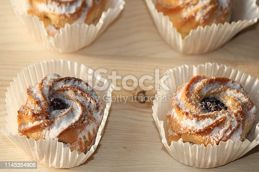 Chocolate muffins on a wooden background, closeup. Selective focus. Delicious muffins sprinkled with powdered sugar in paper cups