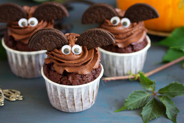 Chocolate muffins, on Halloween. Chocolate muffins, with a chocolate cream in the form of bat on Halloween.Chocolate muffins, with a chocolate cream in the form of bat on Halloween. buttercream stock pictures, royalty-free photos & images