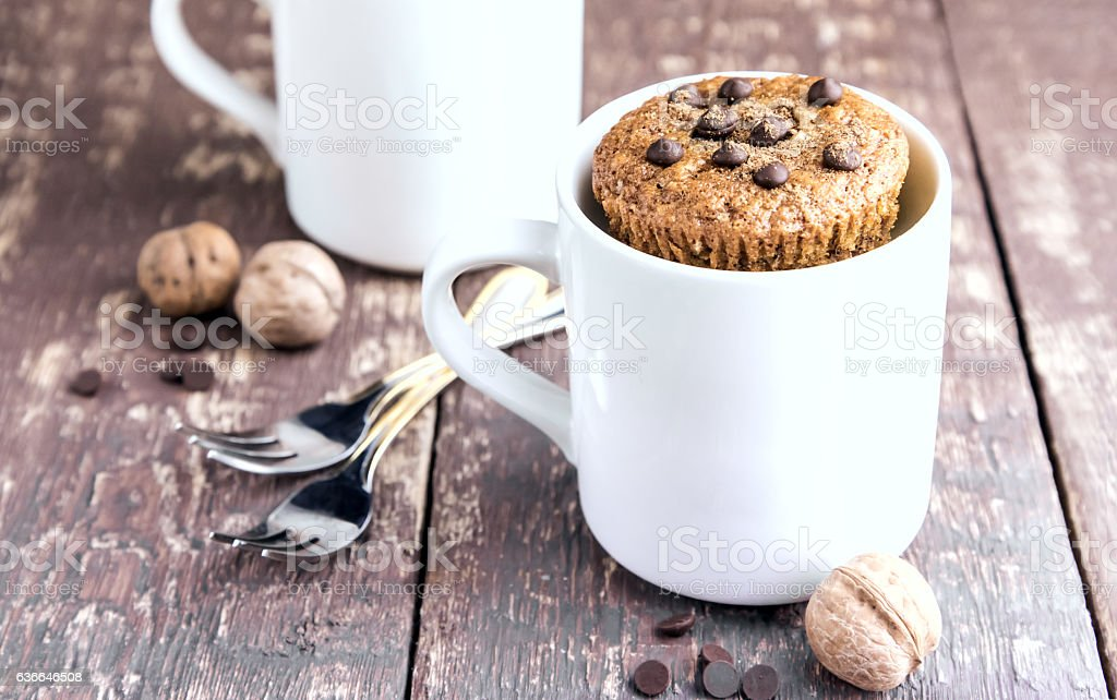 Chocolate muffins with chocolate drops served in white mugs stock photo